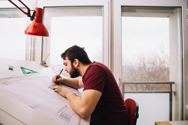 Man carefully making drafts