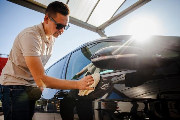 Man carefully polishing a black car