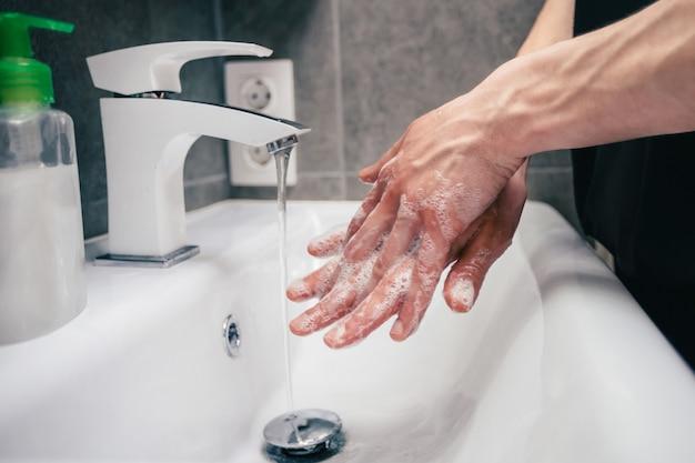 感染症の予防の彼の手の概念を慎重に石鹸で洗う人