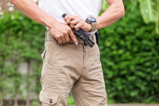Man in cargo pants with gun