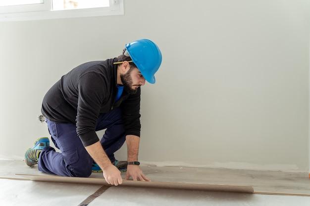남자 목수 조립 라미네이트 바닥재. 집 바닥 리노베이션