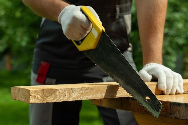 Плотник мужчина распиливает деревянную доску ручной пилой