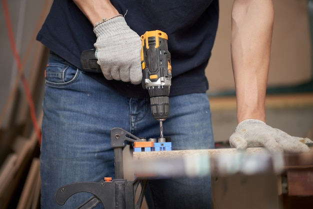 Плотник человек с дрелью и доской в мастерской