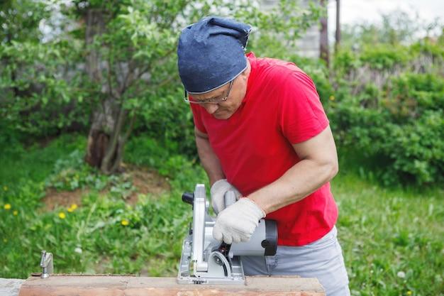 Мужчина карпентер в перчатках пил циркулярной электропилой. красная футболка, серые брюки, на фоне зеленой травы и деревьев. ручная работа, строительство домов, инструменты.