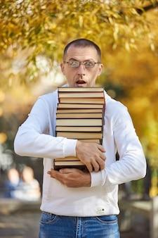 男は手にたくさんの本を持っています訓練のための教科書の山試験の準備