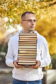 男はたくさんの本を手に持っています。トレーニング用の教科書のスタック。審査の準備