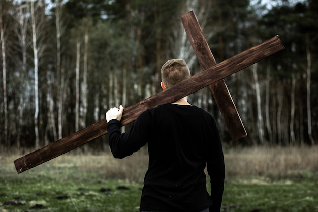 The man carries the cross. ð¡arry the cross. man believes in god. hope in god.