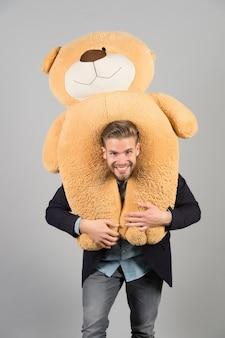 남자는 목, 회색 배경에 거대한 테디 베어를 운반합니다. 생일 선물 개념입니다. 테디 베어 봉제 장난감 즐거운 놀라움. 가이 행복한 수염 난 얼굴은 장난감 테디 베어를 보유하고 있습니다. 남자 정장 정장 귀여운 선물 깜짝.