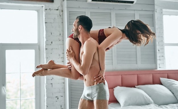 The man carries a happy woman in the bedroom