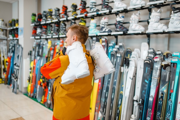 Man carries on his shoulder ski or snowboarding boots in sports shop.