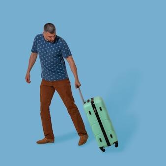 Мужчина несет пластиковый чемодан, держа его за складную ручку.