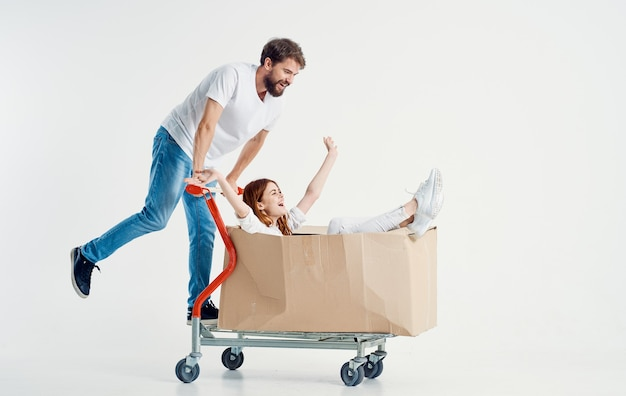 Man carries a woman in a box on a cargo trolley light background fun friends