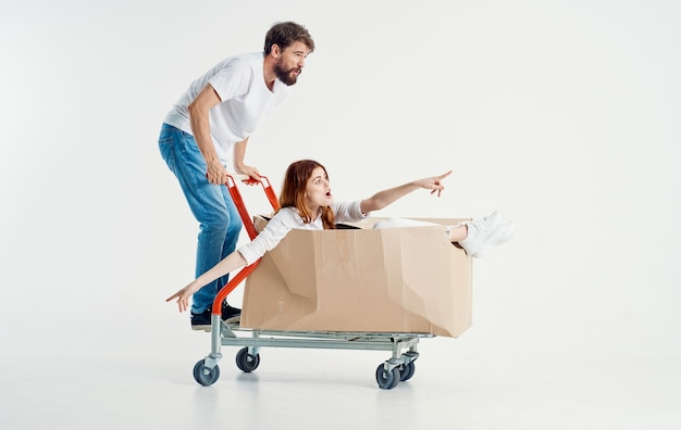 Man carries a woman in a box on a cargo trolley light space fun friends