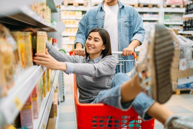 Мужчина несет женщину в тележке, супермаркет