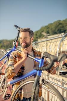 彼の肩に自転車を運ぶ男