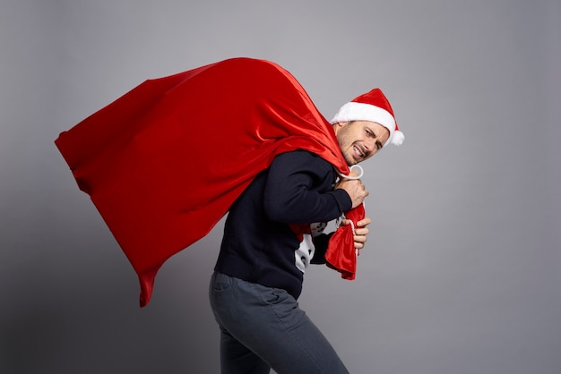 クリスマスプレゼントでいっぱいの巨大なバッグを運ぶ男