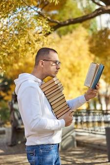 たくさんの本を手に持っている男
