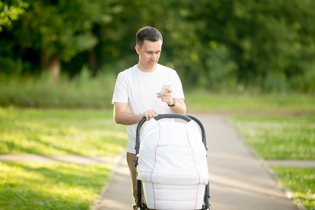 Man carrying a baby stroller while looking a smartphone