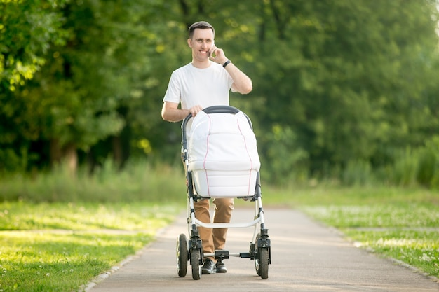 Man carrying a baby stroller white talking on phone