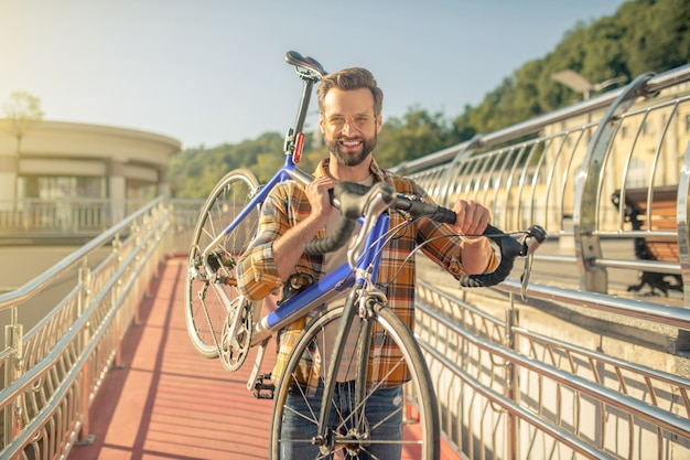 Man carrying a bicycle on his shoulder