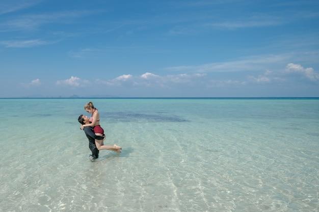 白い砂浜の海の水にビキニの女性を運ぶ男。青い海と空の風景。夏休み。