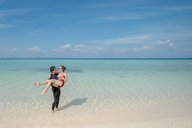 Man carrying bikini woman on sea water by white sand beach. blue sea and sky landscape. summer vacation.