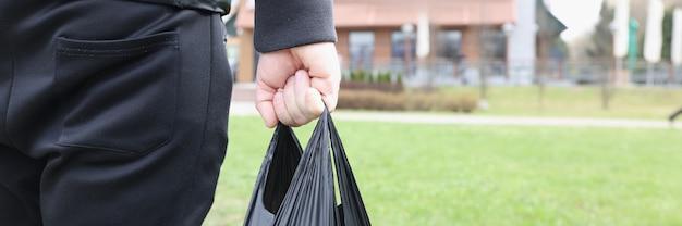 彼の手のクローズアップで食料品と黒いビニール袋を運ぶ男