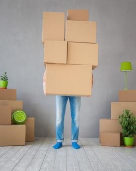 新しい家に箱を運ぶ男。引越しの日と速達のコンセプト