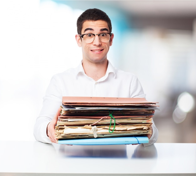 Man carrying a bunch of folders in an office