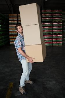 Человек, несущий картонные коробки на складе