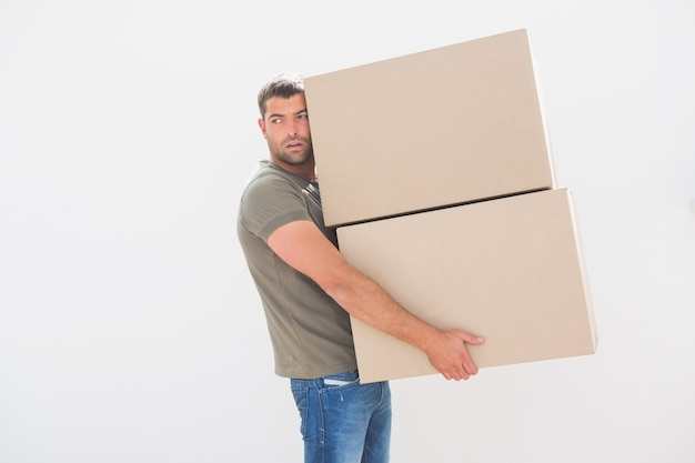 Man carrying cardboard moving boxes at home