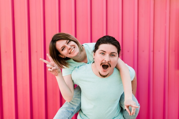 Man carrying her girlfriend piggyback ride on his back against red metal backdrop
