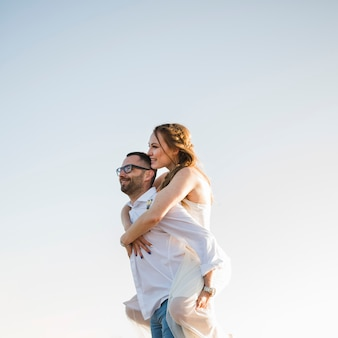 Man carrying his girlfriend on his back at a beach against blue sky