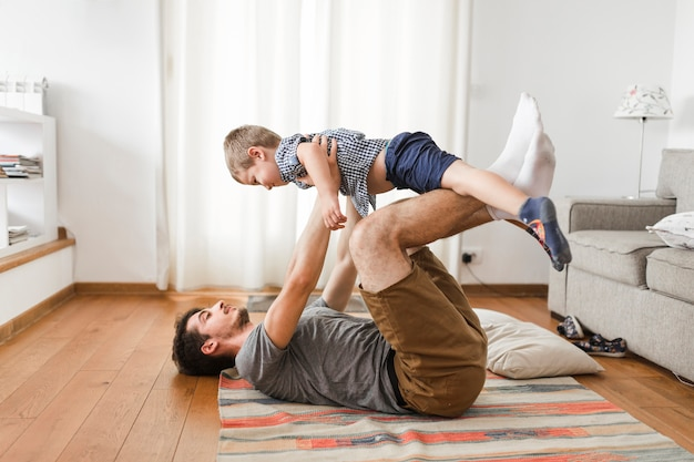 Man carrying his son on leg while exercising