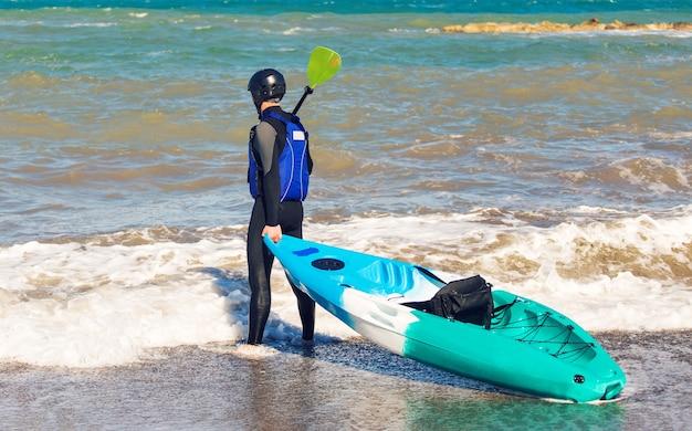 海のビーチでカヤックを運ぶ男