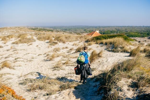 日当たりの良い砂丘でバッグをたくさん運ぶ男