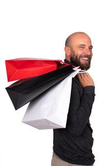 白い背景の上の彼の肩に買い物袋を運ぶ男垂直画像ブラックフライデー