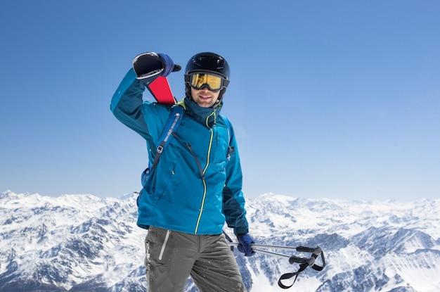スキー用具を運ぶ男