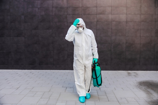 Man carrying sprayer with disinfectant and holding his head. protection from coronavirus concept.