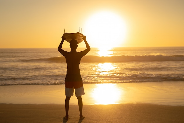 Man carrying surfboard on his head at beach