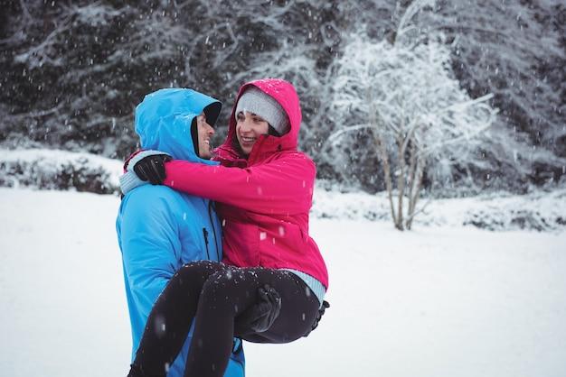 冬の間に森の中で彼の腕の中で女性を運ぶ男