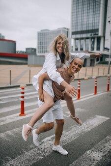 도시에서 야외에서 함께 시간을 보내는 동안 어깨에 젊은 매력적인 여자를 운반하는 사람.
