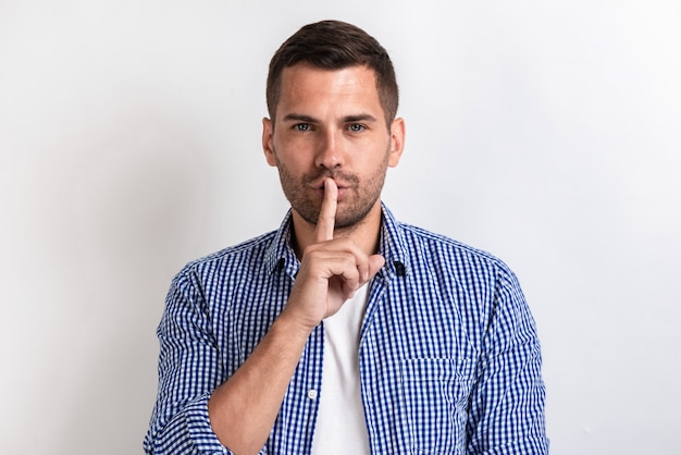 Man in casual clothes gesturing for silence with finger in studio.
