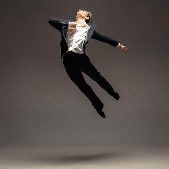 Uomo in abiti casual stile ufficio saltando e ballando isolato su grigio