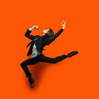 Uomo in abiti casual stile ufficio saltando isolato sulla parete