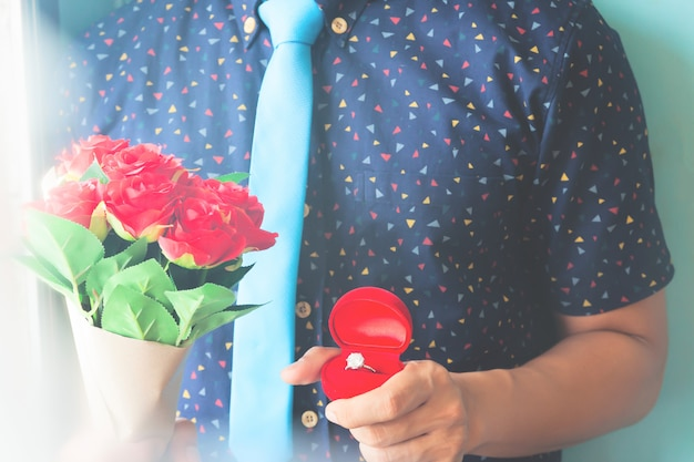 Man in casual shirt and blue color necktie holding diamond ring and red roses