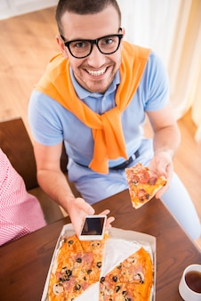 Man in casual style use computers in office and eat pizza