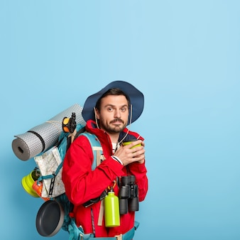 Man in casual wear, drinks coffee, spends free time, carries karemat, holds binoculars, isolated on blue wall, copy space above looks for adventures