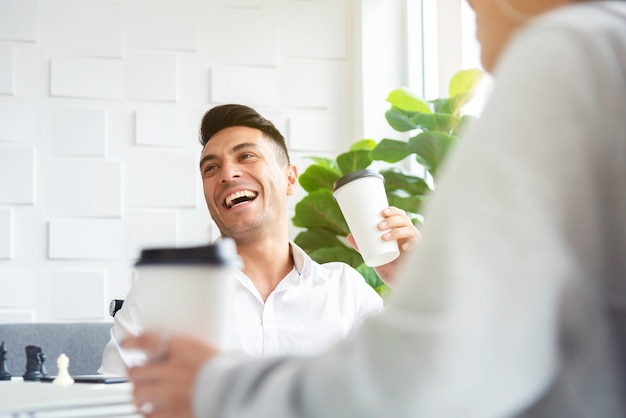 A man in casual white shirt is laughing and drinking while having a meeting with his colle
