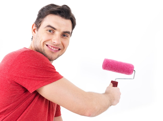 Man in casual with roller and painting wall, portrait on white